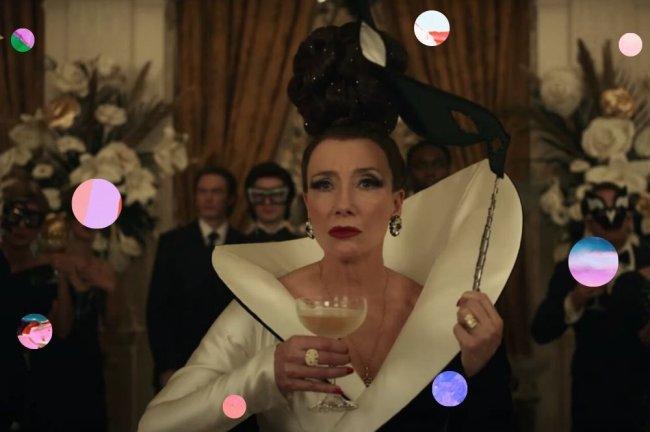 Emma Thompson como Baronesa no filme Cruella, com roupa branca e preta, segurando uma mascara preta e uma taça na outra mão. Sua expressão é séria.