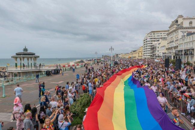 Foto aérea da Parada Gay que aconteceu em Brighton, cidade litorânea da Inglaterra, em 2019. Uma multidão carrega uma imensa banheira com as cores do arco-íris enquanto caminha.