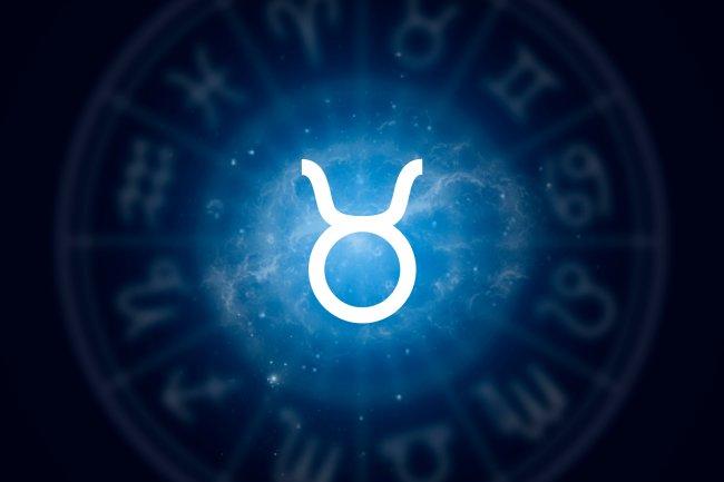 O símbolo astrológico do signo de Touro sobre um fundo azul estrelado com o mapa astral sombreado de fundo