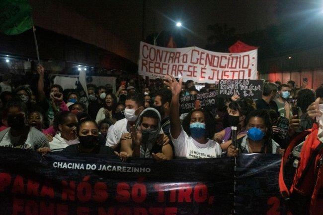 Moradores da favela do Jacarezinho protestam conta chacina e seguram faixas com os escritos: