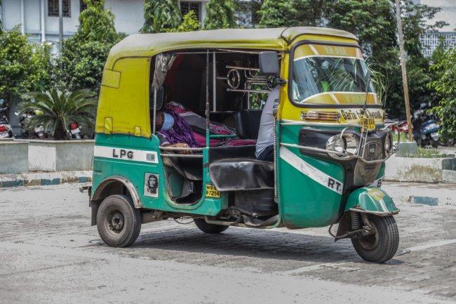 Paciente com COVID-19 sendo transportado em um tuk-tuk, devido à falta de ambulância, em Kolkata, na Índia