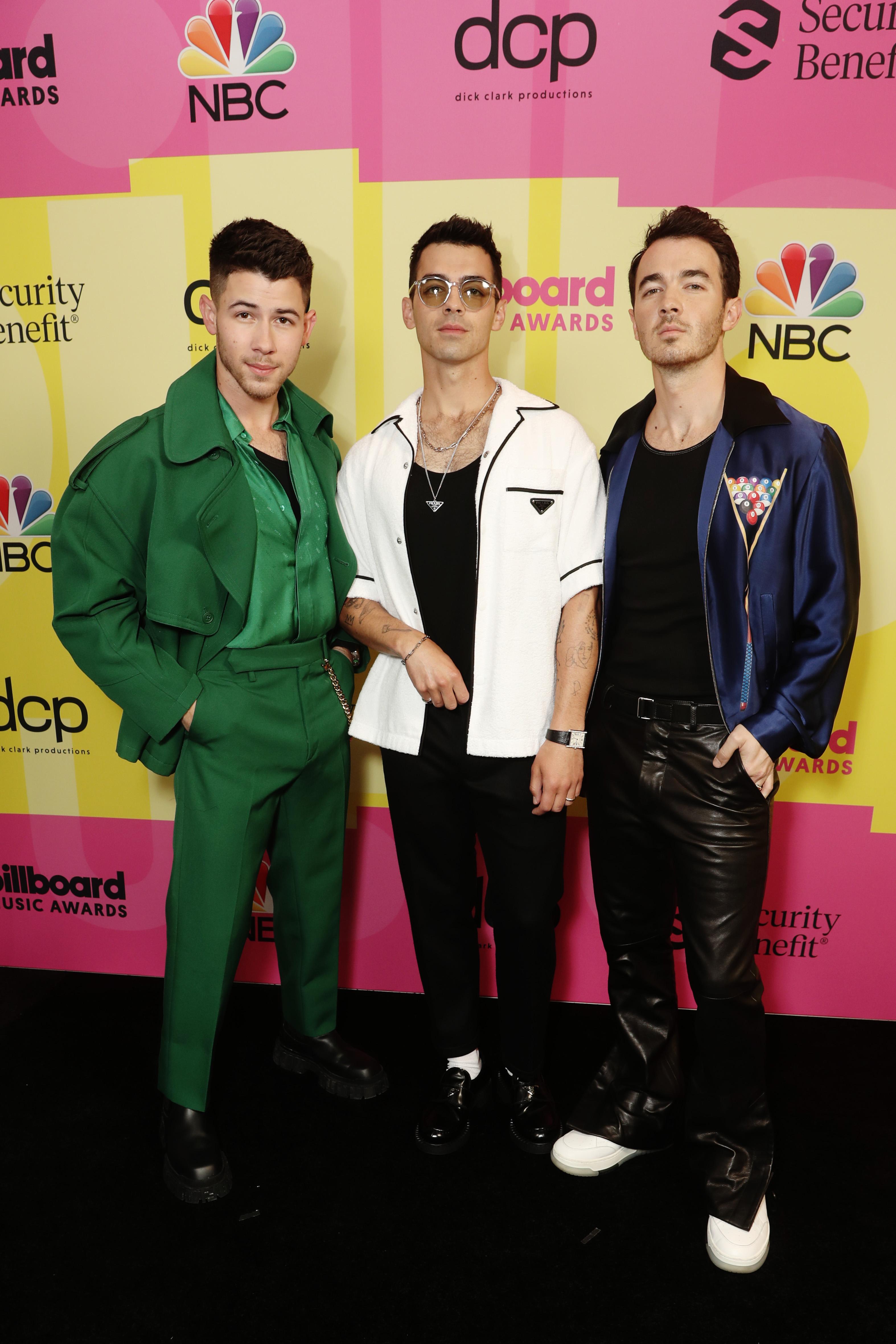 Os Jonas Brothers no Billboard Music Awards 2021. Nick Jonas está com um look todo verde bandeira, Joe Jonas está de preto com uma camisa branca por cima, e Kevin Jonas está de preto com uma jaqueta azul-marinho.