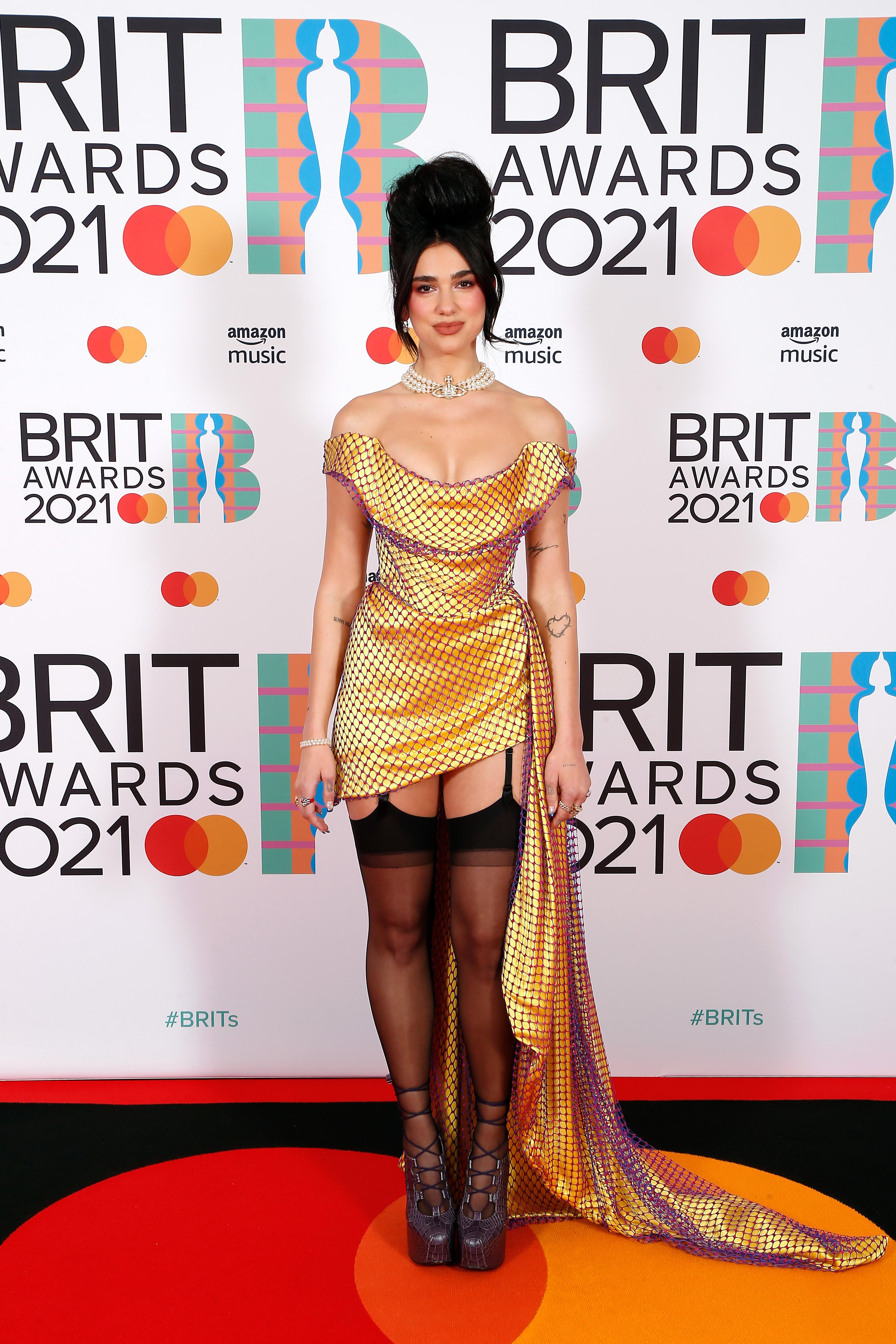 Dua Lipa no tapete vermelho do BRIT Awards 2021. Ela está com um leve sorriso sem mostrar os dentes, usando um vestido dourado com uma rede de furinhos roxos por cima, uma meia-calça preta e um sapato de salto. Também está com colar de pérolas e cabelo preso em um coque alto bem volumoso.