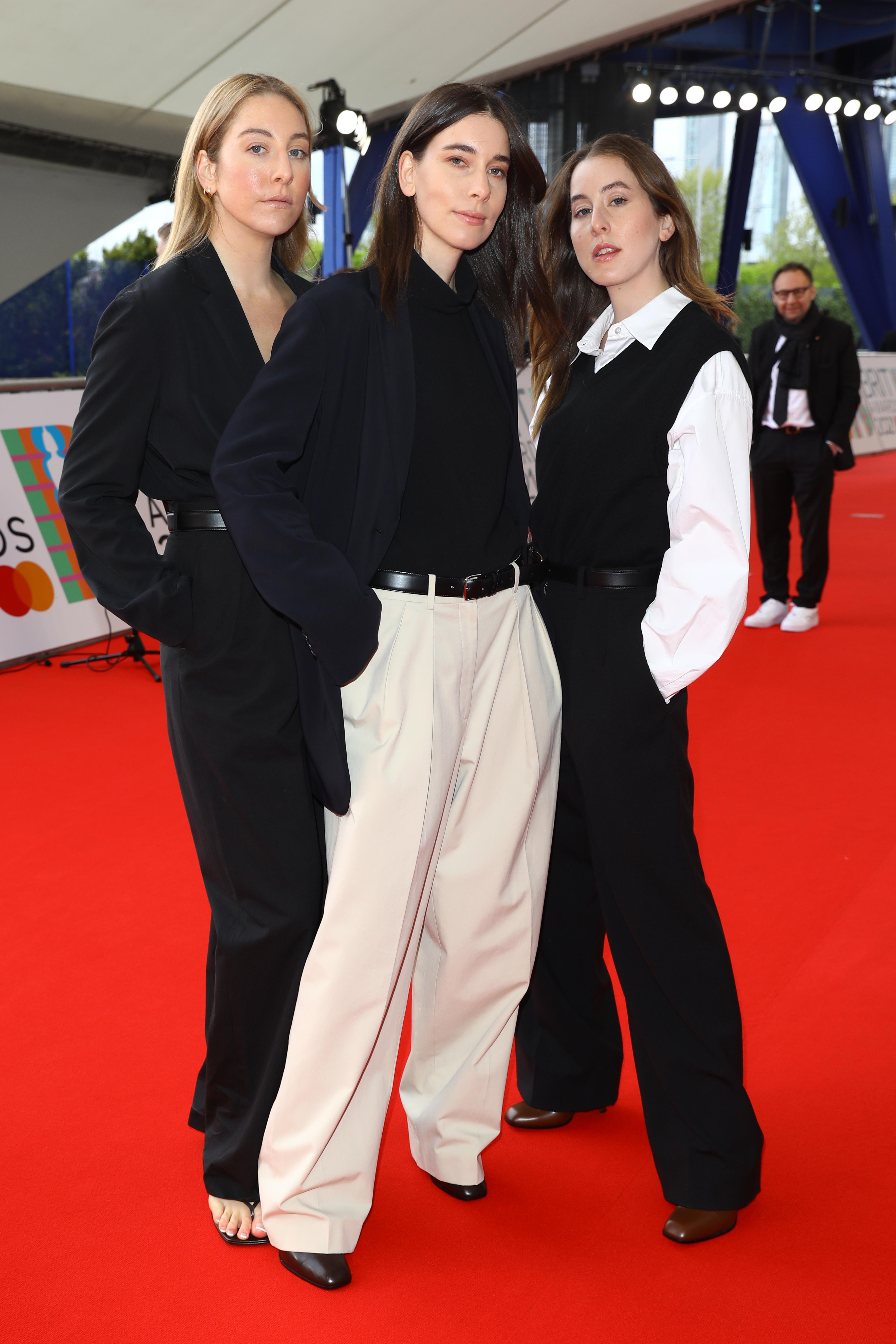 As irmãs Haim no BRIT Awards 2021. À esquerda, Este Haim está com um look todo preto formado por camisa e calça de alfaiataria. No meio, Danielle Haim usa calça bege, cinto preto e camisa e blaze pretos. À direita, Alana Haim usa camisa branca por baixo de colete preto e calça preta. Todas estão com expressão facial séria.