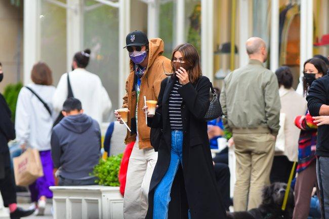 Jacob Elordi e Kaia Gerber andando na rua com café na mão e usando máscara
