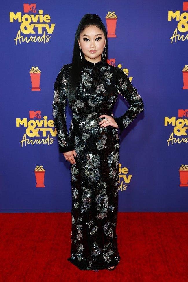 Atriz Lana Condor no MTV Movie & TV Awards, usando vestido longo e preto com detalhes em prata, posando com uma mão na cintura e expressão sorridente no red carpet da premiação