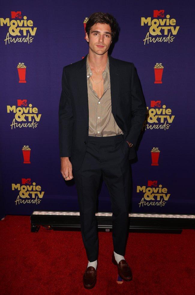 Jacob Elordi no MTv Movie & TV Awards, posando com expressão séria no red carpet da premiação usando terno preto e camisa levemente marrom.