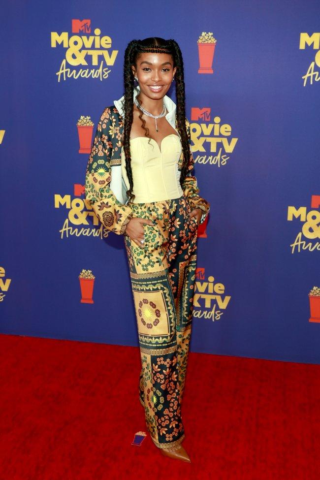 Atriz Yara Shahidi no MTV Movie & TV Awards, usando corset amarelo e conjunto estampado, posando com expressão sorridente.