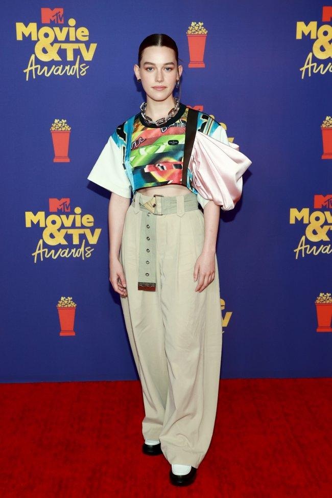 Atriz Victoria Pedretti no MTV Movie & TV Awards usando blusa verde com detalhes coloridos e manga bugante, calça bege, posando com os braços esticados ao lado do corpo e com expressão levemente sorridente.
