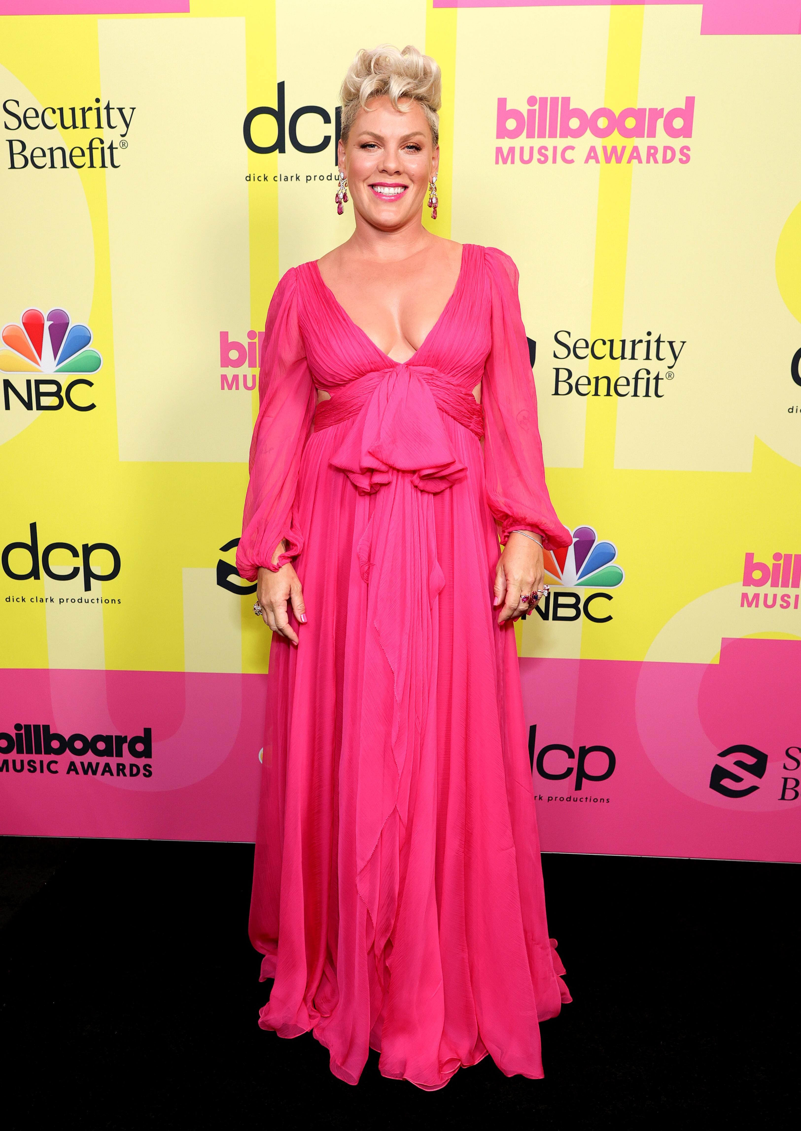 Pink usando vestido longo rosa esvoaçante no Billboard Music Awards 2021. Ela está sorrindo e olhando para a câmera.