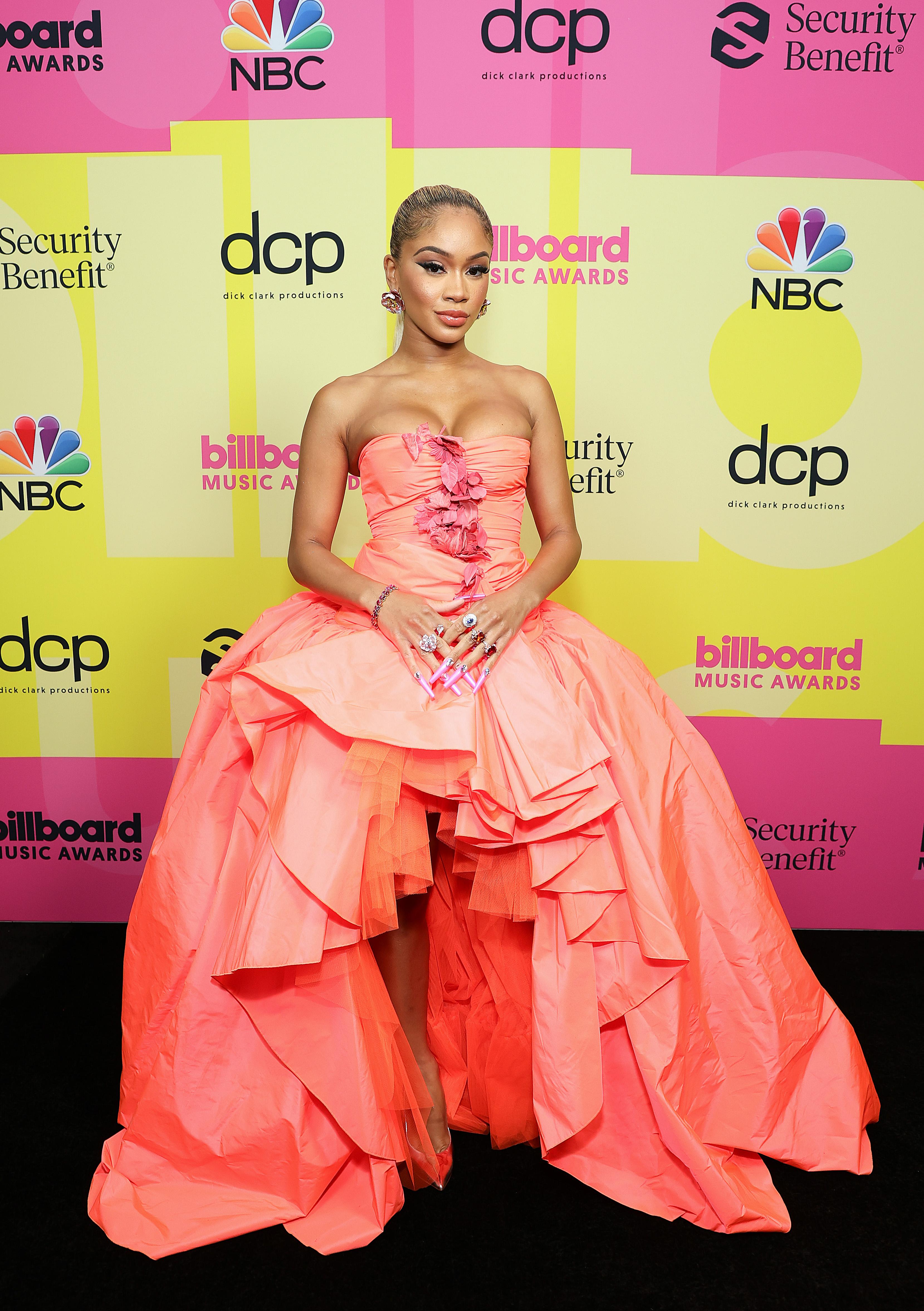 Saweetie no Billboard Music Awards 2021. Ela está usando um vestido laranja sem alças com saia volumosa e abertura na parte da frente.
