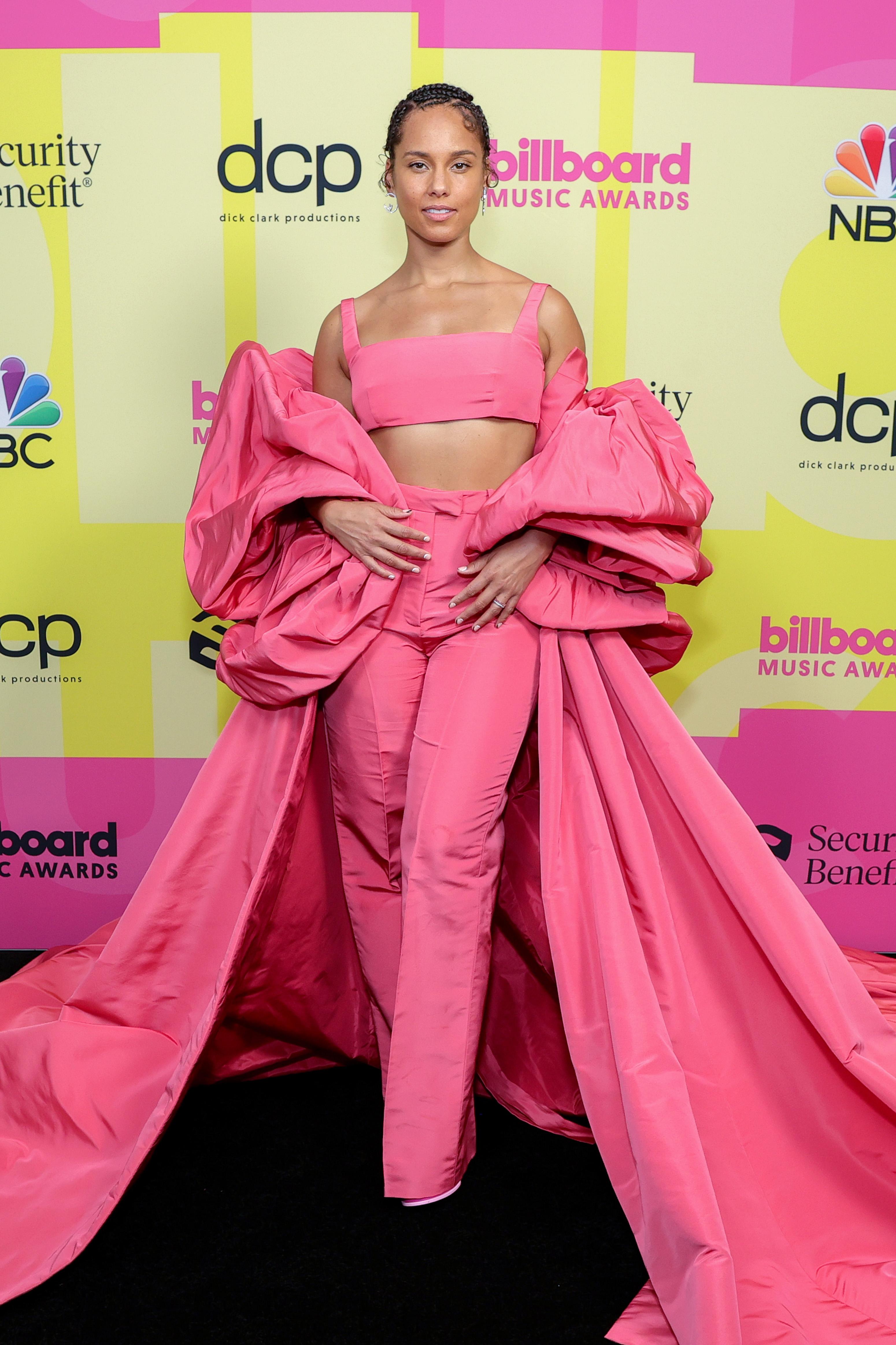 Alicia Keys no Billboard Music Awards 2021. Ela está usando um look todo rosa com top cropped, calça de alfaiataria e uma espécie de capa volumosa por cima.