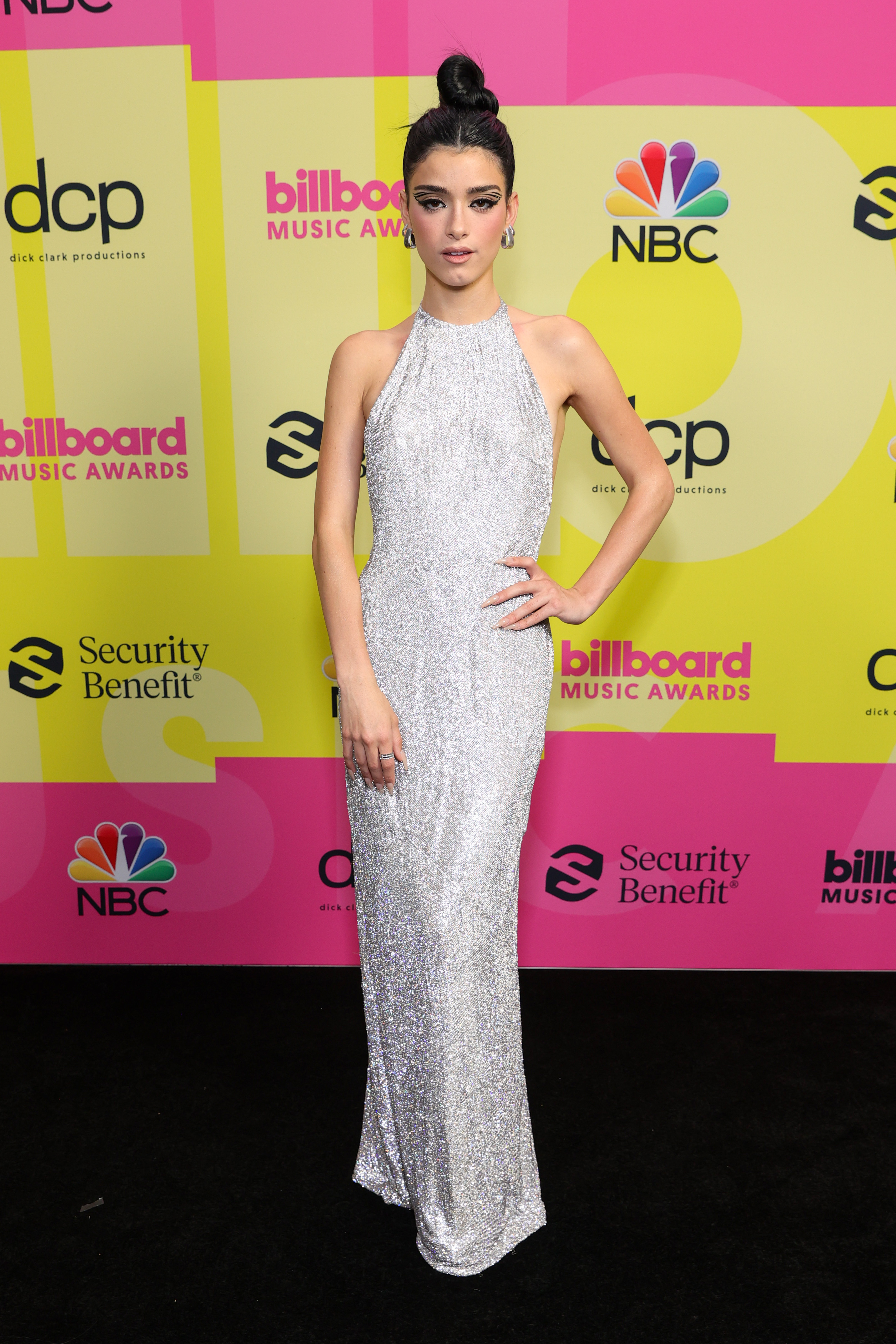 Dixie D'Amelio no Billboard Music Awards 2021. Ela está usando um vestido longo prateado, um penteado com coque e maquiagem com delineado grácio. Sua expressão facial é séria e uma das mãos está na cintura.