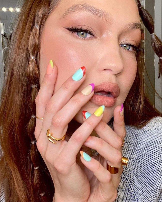 Gigi Hadid com nail art de francesinha colorida, posando com as mãos no rosto para evidenciar as unhas, suas unhas estão com esmalte azul, amarelo, laranja, roxo e rosa. Sua expressão é seria. Nos cabelos ela tem duas mechas com bubble hair.