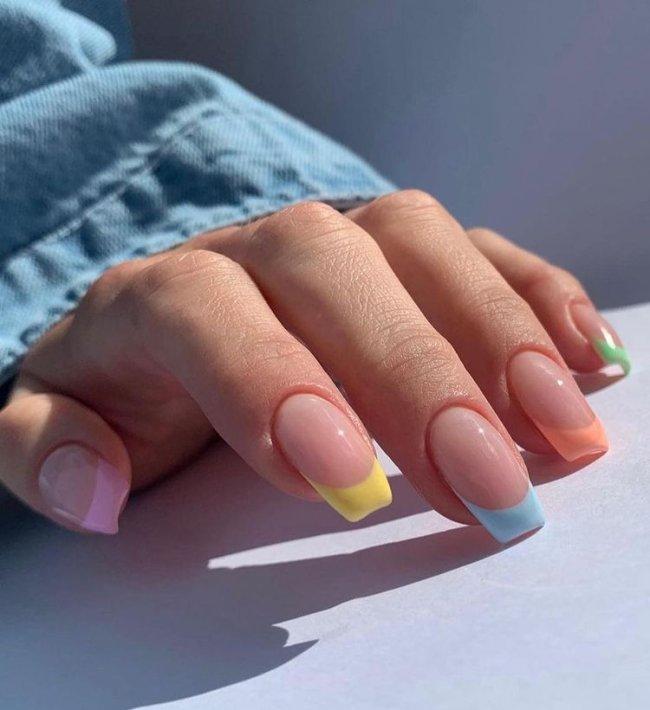 Foto mostrando uma mão com os dedos dobrados para evidenciar as unhas pintadas em francesinha colorida nas cores laranja, azul, rosa, verde e amarelo.