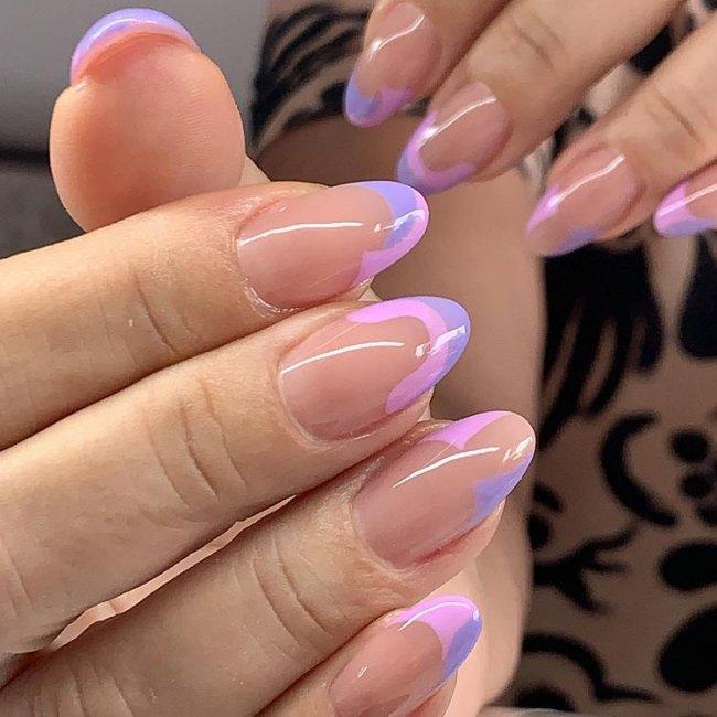 Foto mostrando uma mão com os dedos dobrados para evidenciar as unhas pintadas em francesinha colorida lilás