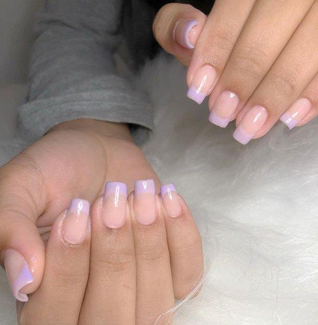 Foto mostrando uma mão com os dedos dobrados para evidenciar as unhas pintadas em francesinha colorida na cor lilás.