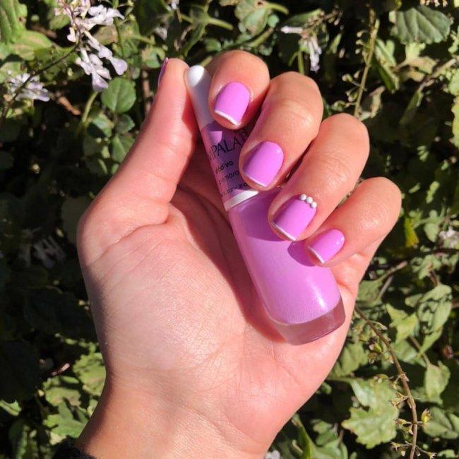 Foto mostrando uma mão com os dedos dobrados para evidenciar as unhas pintadas em francesinha colorida nas cores rosa e branco.