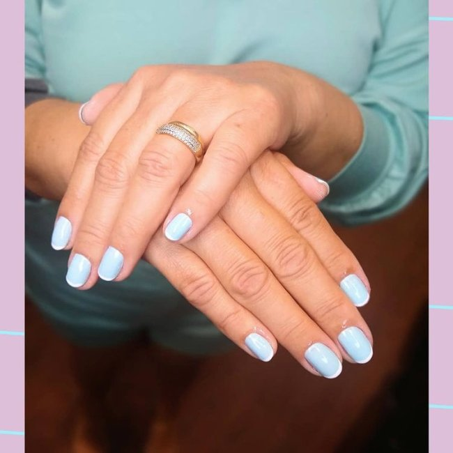 Foto mostrando uma mão com os dedos dobrados para evidenciar as unhas pintadas em francesinha colorida nas cores azul e branco.