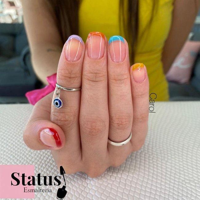 Foto mostrando uma mão com os dedos dobrados para evidenciar as unhas pintadas em francesinha colorida nas cores cinza, laranja, lilas, amarelo e vermelho.
