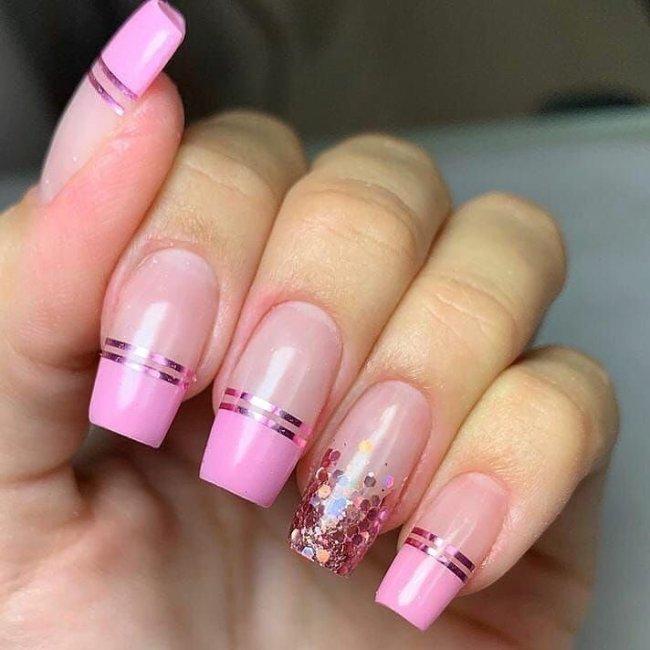 Foto mostrando uma mão com os dedos dobrados para evidenciar as unhas pintadas em francesinha colorida com glitter e rosa