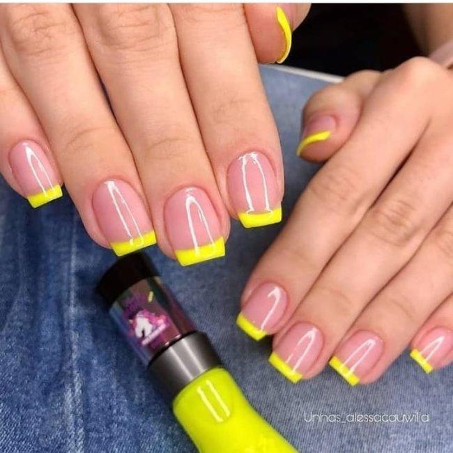 Foto mostrando uma mão com os dedos dobrados para evidenciar as unhas pintadas em francesinha colorida amarela