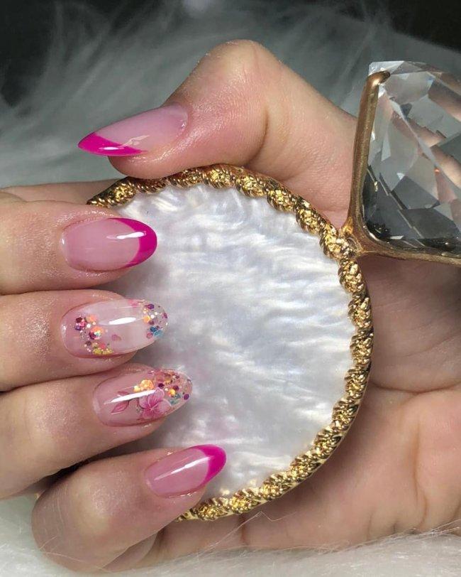 Foto mostrando uma mão com os dedos dobrados para evidenciar as unhas pintadas em francesinha colorida rosa e com detalhes em glitter