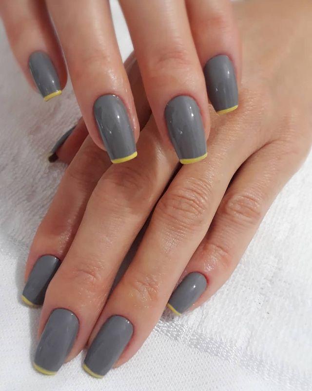 Foto mostrando uma mão com os dedos dobrados para evidenciar as unhas pintadas em francesinha colorida amarela com base cinza