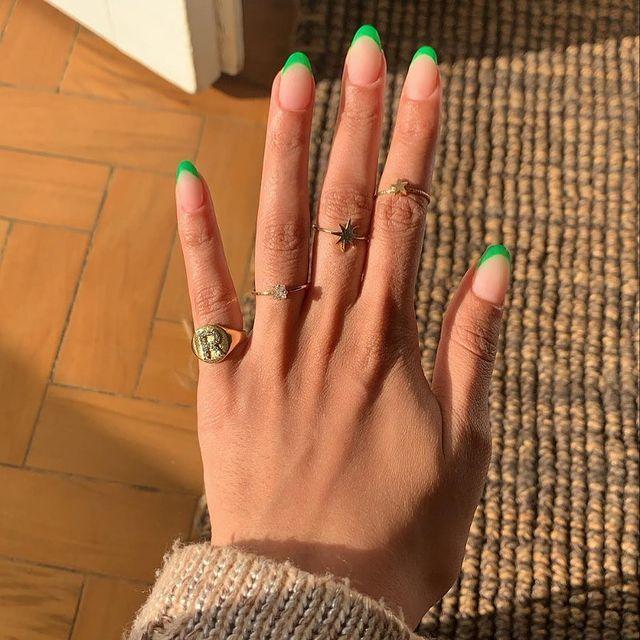 Foto mostrando uma mão com os dedos dobrados para evidenciar as unhas pintadas em francesinha colorida na cor verde.