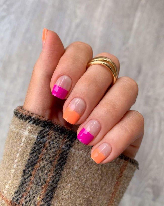 Foto mostrando uma mão com os dedos dobrados para evidenciar as unhas pintadas em francesinha colorida nas cores laranja e rosa