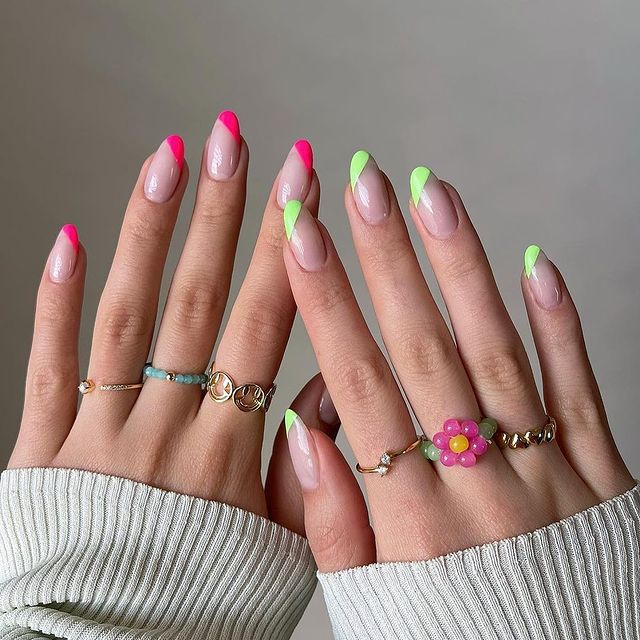 Foto mostrando uma mão com os dedos dobrados para evidenciar as unhas pintadas em francesinha colorida sendo uma das mãos com a unha rosa e a outra verde.