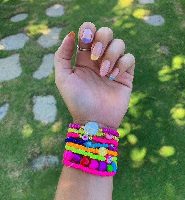 Foto mostrando uma mão com os dedos dobrados para evidenciar as unhas pintadas em francesinha colorida nas cores amarela, rosa, azul, lilas e laranja.