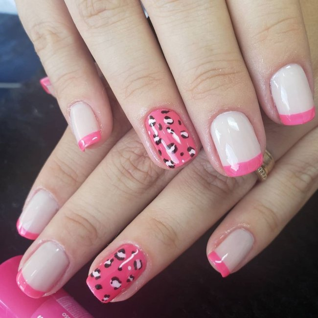 Foto mostrando uma mão com os dedos dobrados para evidenciar as unhas pintadas em francesinha colorida rosa, sendo uma das unhas filha única com animal print