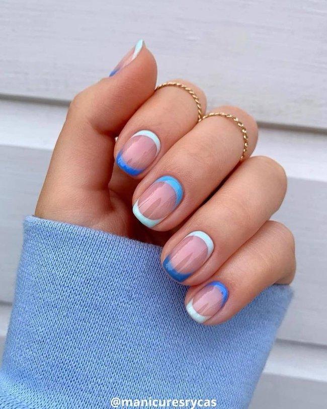 Foto mostrando uma mão com os dedos dobrados para evidenciar as unhas pintadas em francesinha colorida com a ponta e o começo da unha pintados com detalhes azul.