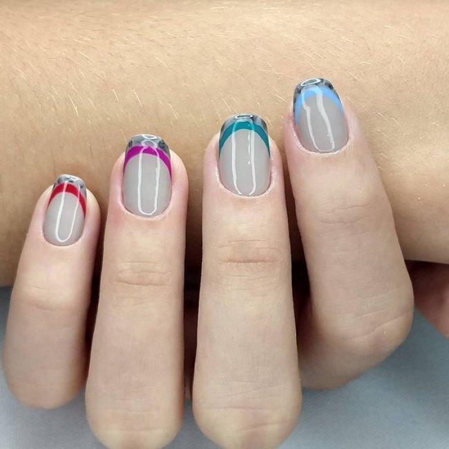 Foto mostrando uma mão com os dedos dobrados para evidenciar as unhas pintadas em francesinha colorida; com base cinza e linhas coloridas, em roxo, vermelho, cinza e verde.