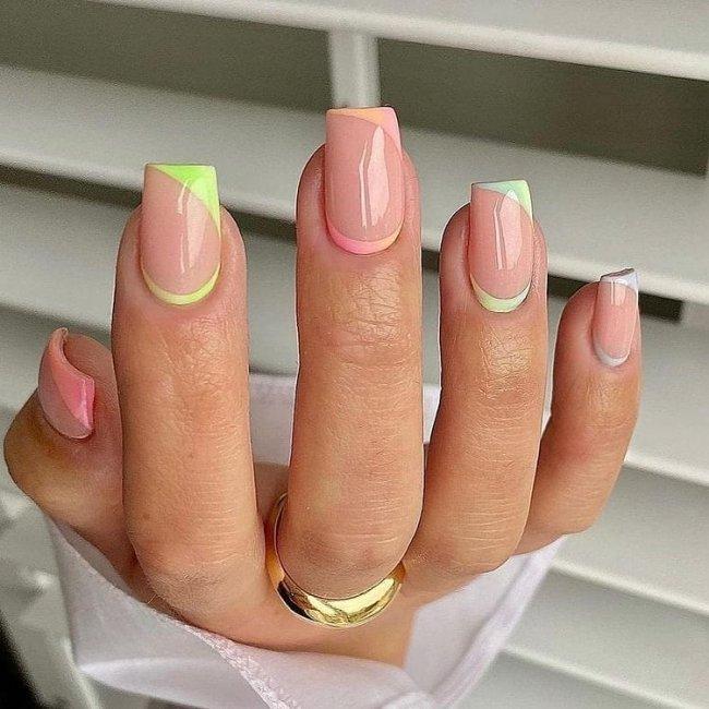 Foto mostrando uma mão com os dedos dobrados para evidenciar as unhas pintadas em francesinha colorida nas cores verde, laranja e lilas.