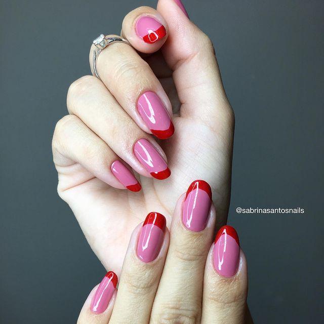 Foto mostrando uma mão com os dedos dobrados para evidenciar as unhas pintadas em francesinha colorida nas cores rosa e vermelho.
