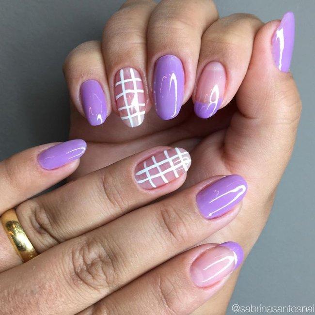 Foto mostrando uma mão com os dedos dobrados para evidenciar as unhas pintadas em francesinha colorida lilás com detalhes quadriculado branco