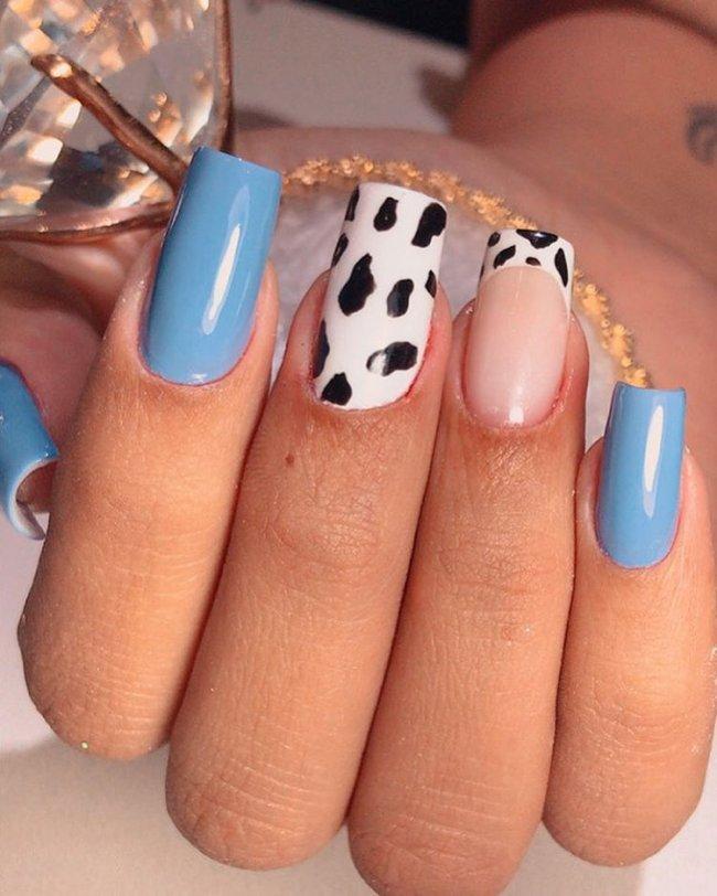 Foto mostrando uma mão com os dedos dobrados para evidenciar as unhas pintadas em francesinha colorida nas cores azul, e uma unha filha única com estampa animal print e outra com francesinha usando animal print.
