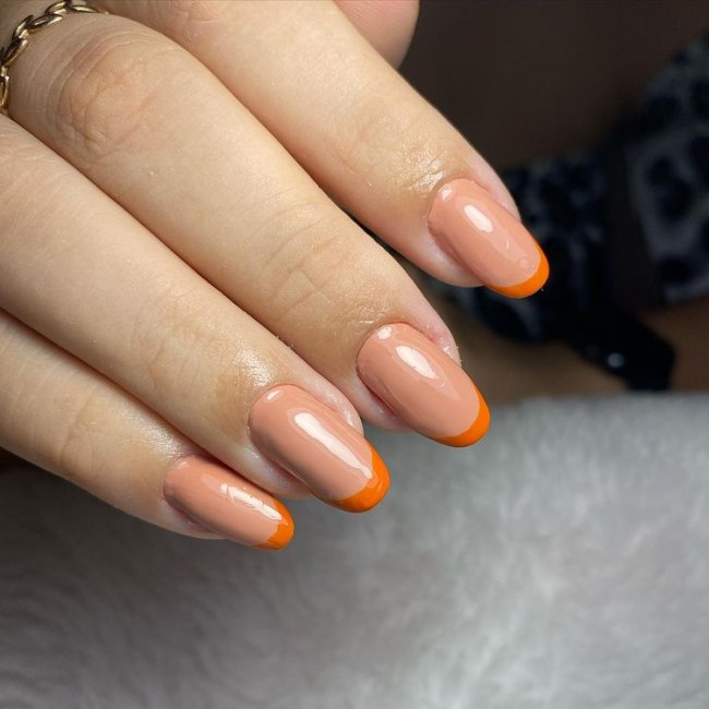 Foto mostrando uma mão com os dedos dobrados para evidenciar as unhas pintadas em francesinha colorida; com base laranja claro e francesinha com laranja escuro.