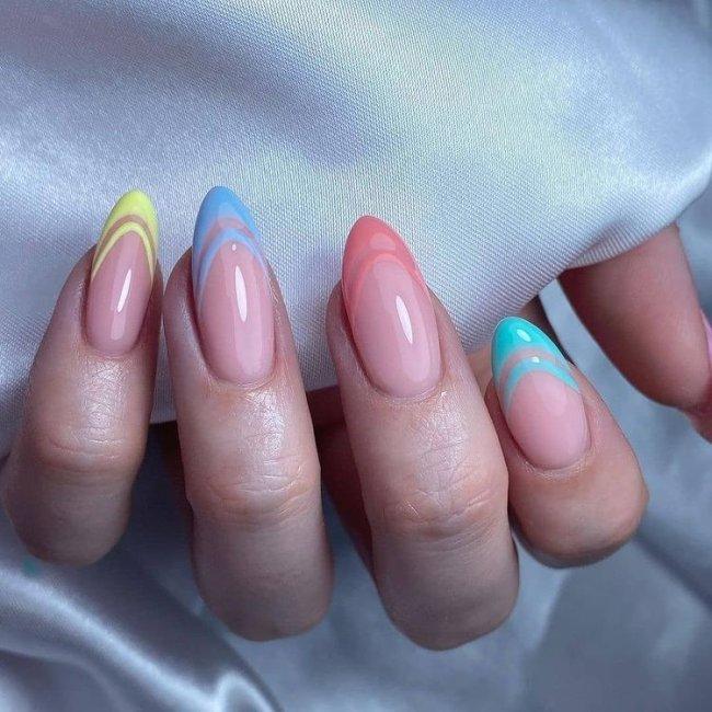 Foto mostrando uma mão com os dedos dobrados para evidenciar as unhas pintadas em francesinha colorida nas cores azul, amarelo, bege e azul mais claro.