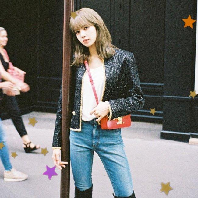 Lisa, integrante do grupo Blackpink, posando para foto encostada em um ferro, usando blazer preto, bolsa vermelha, calça jeans e bota preta. Sua expressão é séria.