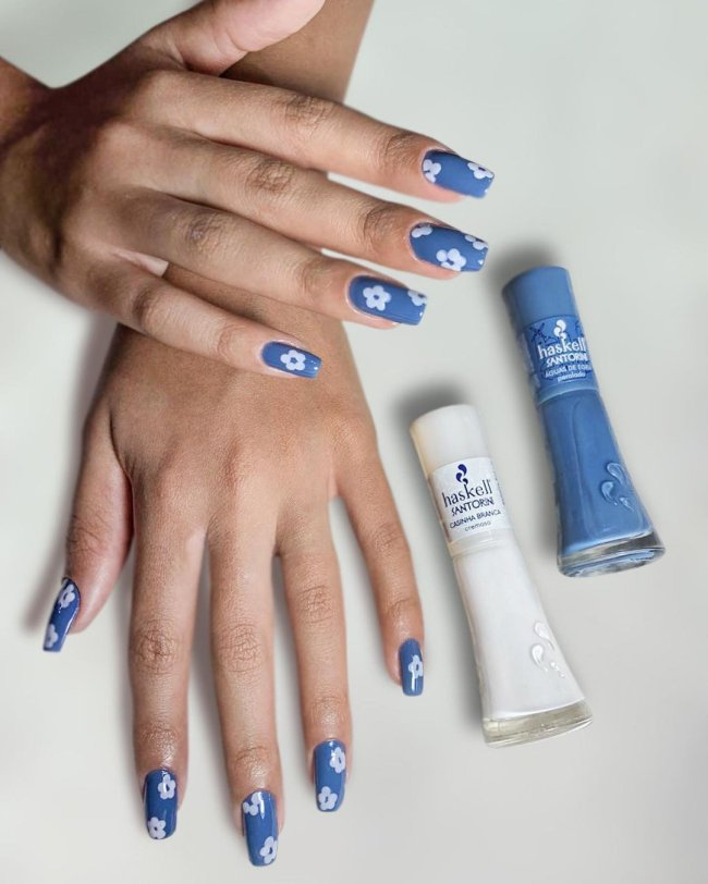 Duas mãos ao lado de um esmalte branco e outro azul. Nas unhas com florzinha branca e fundo azul.