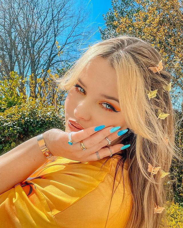 Jovem com expressão séria, com uma das mãos no rosto, unhas azuis, usando camiseta amarela e posando de lado, atrás da jovem podemos ver o céu azul e árvores.