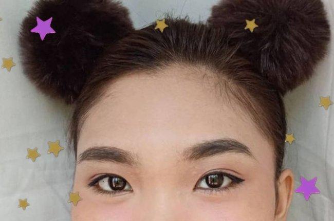 Foto com close no olhar da jovem, que usa coques nas laterais da cabeça.
