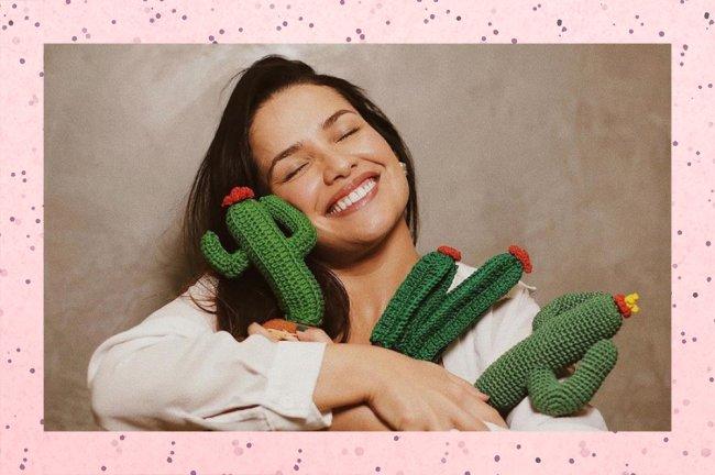 Juliette está sorrindo com os olhos fechados, abraçada com três almofadas de cactos,