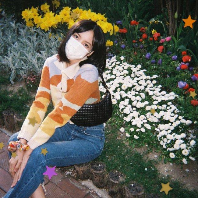 Lisa, integrante do grupo Blackpink, sentada perto de flores brancas, vermelhas e amarelas. Usando camisa listrada azul clara, laranja e amarela. Calça jeans, e bolsa baguete preta. Não conseguimos ver sua expressão pois Lisa está usando uma máscara de proteção branca.
