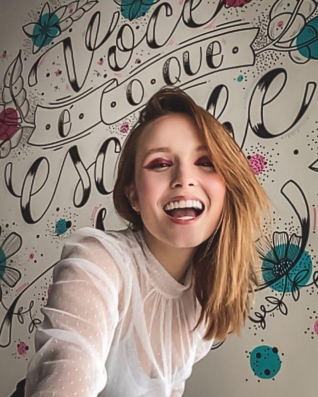 Larissa Manoela com cabelo médio, sorridente com blusa branca e posando em frente uma parede com palavras em preto.