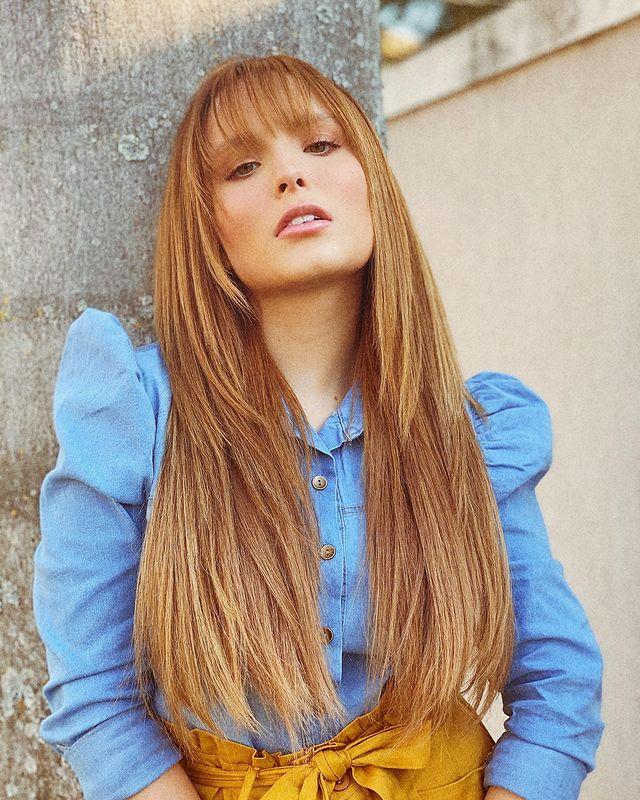 Larissa Manoela com expressão séria, posando para foto com a cabeça levemente levantada com camisa jeans com manga bufante.