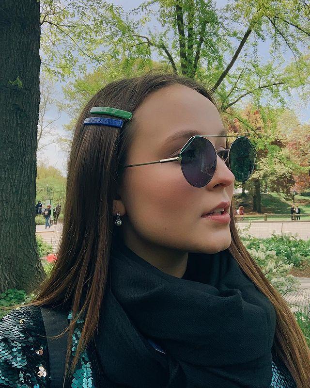 Larissa Manoela olhando para o lado com expressão séria e óculos preto circular, com cachecol preto.